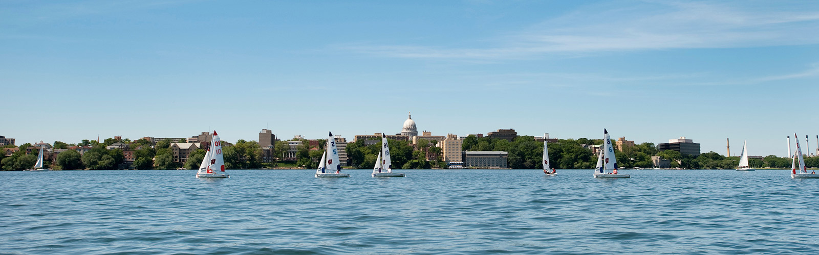 Ho的er sailboats sail on Lake Mendota with the state capitol building in the background.