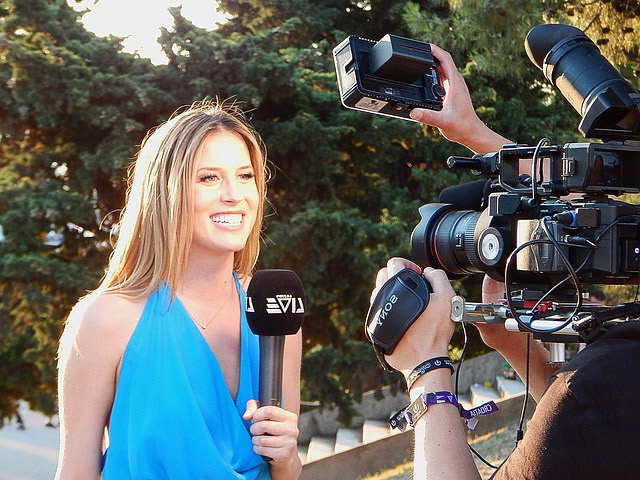 Reporter being filmed while holding microphone